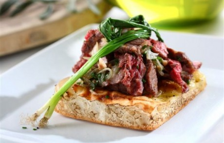 מתכון לסעודה מפסקת: נתחי אנטריקוט צלויים, בצל מטוגן, כמון ופטרוזיליה על פיתה אפויה בשמן זית